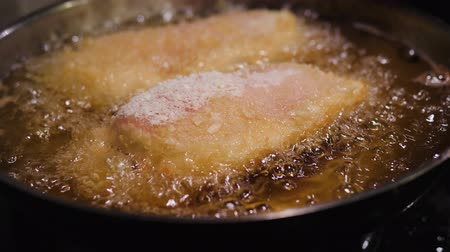 chicken recipes : cordon blue fried in oil in a frying pan. Chicken cordon bleu frying in hot oil, battered in bread crumbs