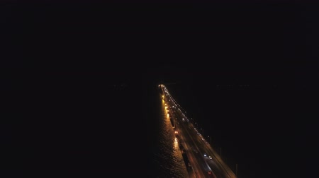 asma : aerial view lighted bridge at night with highways and cars. suspension bridge over madura strait with highway and car, surabaya. aerial view bridge Suramadu connecting islands Java and Madura. High coast bridge with highway.java, indonesia