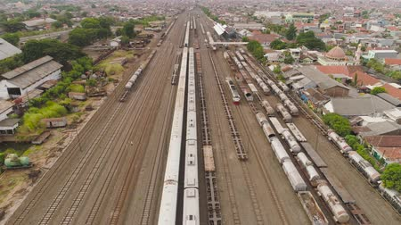 транзит : freight train with cisterns and containers on railway station Surabaya Indonesia. Wagons with goods on railroad. Heavy industry. railway station in an asian city among buildings.