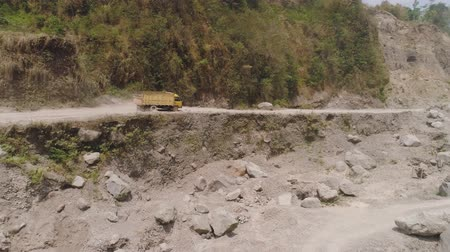 giant wheel : heavy truck carrying cargo on mountain dirt road to the gorge. aerial view canyon off-road construction truck