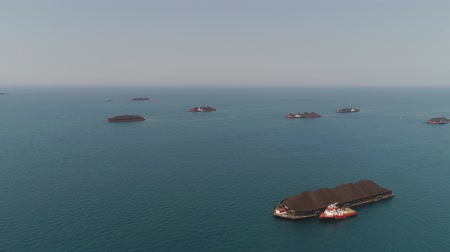 arrasto : aerial view barges full coal anchored at sea near coal fired power station waiting be transported. coal barges and tugboats java, paiton indonesia Vídeos