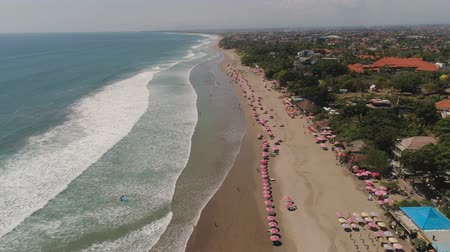 surfista : Aerial view sand beach with resting people, hotels and tourists, sun umbrellas, Bali, Kuta. surfers on water surface. Seascape, beach, ocean, sky sea Travel concept