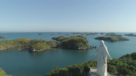 pilgrimage : Statue of Jesus Christ on Pilgrimage island in Hundred Islands National Park, Pangasinan, Philippines. Aerial view of group of small islands with beaches and lagoons, famous tourist attraction, Alaminos.