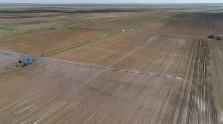spil : Aerial view of Crop Irrigation using the center pivot sprinkler system. An irrigation pivot watering agricultural land. Irrigation system watering farm land.