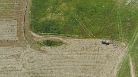 polního : Aerial, view agricultural machinery with wheeled rake makes ranks beveled hay.Tractor which is lining up dried grass getting it ready for pickup so it can be used as animal fodder summer day. Dostupné videozáznamy