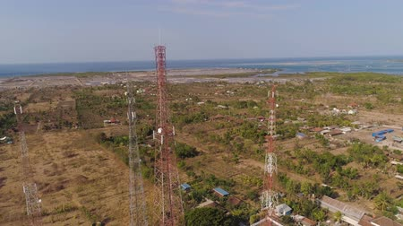 transmitir : aerial view cell phone towers line in bali, indonesia. Telecommunication tower, communication antenna on coast sea Vídeos