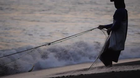 fisch netz : fisherman pulling nets from sea at sunset on sandy beach. Fisherman catching fish in ocean.
