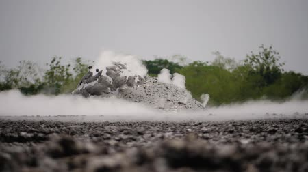enxofre : mud volcano with bursting bubble bledug kuwu. volcanic plateau with geothermal activity and geysers, slow motion Indonesia java. volcanic landscape