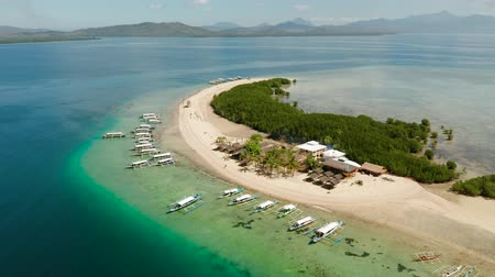 island hopping : Island and sandy beach with tourists, sand bar surrounded by coral reef and blue sea in the honda bay, aerial drone. Tropical island and coral reef. starfish island. Summer and travel vacation concept, Philippines, Palawan Stock Footage