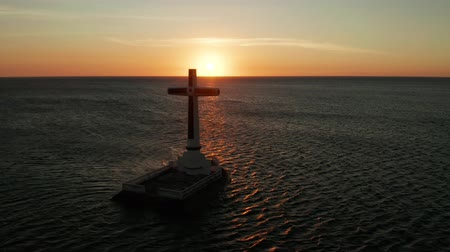 мрачный : Catholic cross in sunken cemetery in the sea at sunset, aerial drone. Large crucafix marking the underwater sunken cemetary, Camiguin Island Philippines. Стоковые видеозаписи