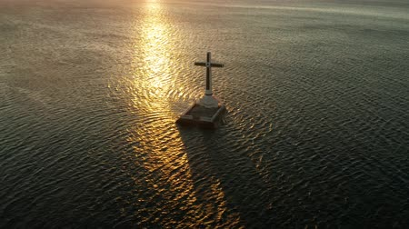 homály : Catholic cross in sunken cemetery in the sea at sunset, aerial drone. Large crucafix marking the underwater sunken cemetary, Camiguin Island Philippines. Stock mozgókép