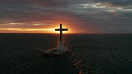 crucifix : Catholic cross in sunken cemetery in the sea at sunset, aerial view. Colorful bright clouds during sunset over the sea. Sunset at Sunken Cemetery Camiguin Island Philippines.