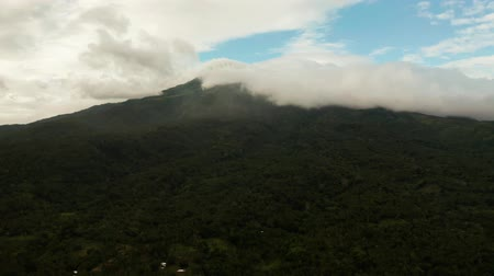 mindanao : Aerial view of tops of the mountains covered with clouds in the evening Camiguin, Philippines. Mountain landscape on tropical island with mountain peaks covered with forest. Slopes of mountains with evergreen vegetation.