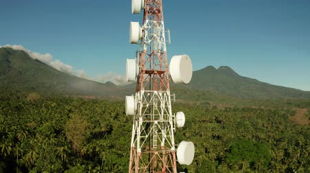 reflektör : Antennas and microwaves link dishes of mobile phone network and TV transmitter on telecommunication towers with mountains and rainforest. Camiguin, Philippines