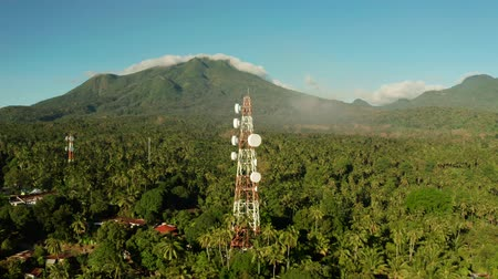 vysílač : Antennas and microwaves link dishes of mobile phone network and TV transmitter on telecommunication towers with mountains and rainforest. Camiguin, Philippines