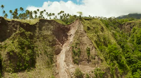 ambientalmente : Mountain landslide and rock falls in an environmentally hazardous area. Large cracks in earth, Descent of large layers of earth blocking road. Soil under condition of the erosion as the cliff by human Vídeos