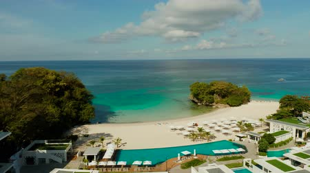 masmavi : Tropical sandy beach and bay with azure water at the hotel with swimming pool and sun beds Boracay, Philippines. Seascape with beach on tropical island. Summer and travel vacation concept.