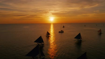 yansıyan : Sunset over the sea surface with sailing boats from above Boracay, Philippines. Reflected sun on a water surface. Sunset over ocean. Seascape, Summer and travel vacation concept Stok Video