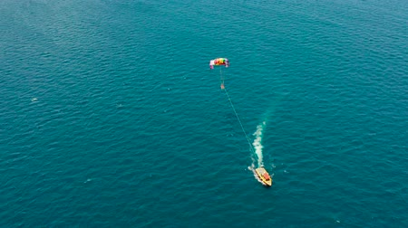 parachuting : Tourists on a parachute over the sea, aerial view. Tourists parasailing on the Boracay, Philippines. Stock Footage