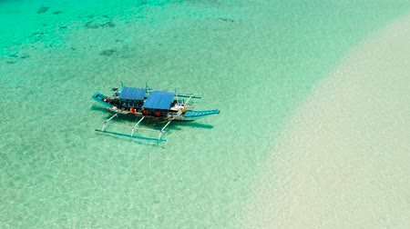balabac : Boat on a tropical beach in the turquoise water of the lagoon from above. Summer and travel vacation concept. Mansalangan sandbar. Beach at the atoll. Balabac, Palawan, Philippines.