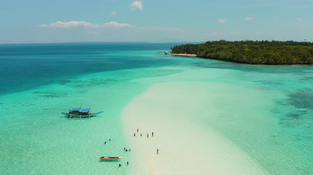 costa azzurra : Island with a sandy beach and azure water surrounded by a coral reef and an atoll, aerial view. Mansalangan sandbar, Balabac, Palawan, Philippines. Summer and travel vacation concept Filmati Stock
