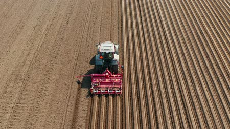 furrow : aerial view tractor cuts furrows in farm field for sowing farm tractor with rotary harrow plow preparing land for sowing. Tractor with harrows prepares the agricultural land for planting crop. Cultivation of farmland by disc harrows.