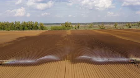 орошение : aerial view crop irrigation machine using center pivot sprinkler system. An irrigation pivot watering agricultural land. Irrigation system watering farm land.