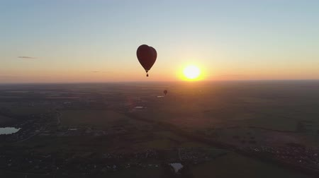globos de aire caliente : Aerial view Hot air balloon shape heart in sky over field in countryside, beautiful sky and sunset. Aerostat fly over countryside.Aerial footage 4K