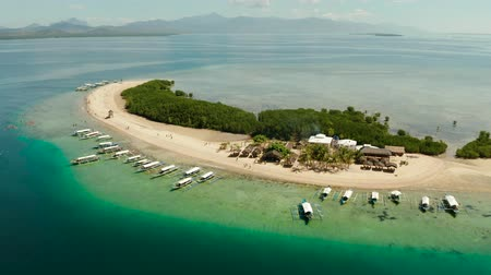 starfish : Tropical island and sandy beach with tourists surrounded by coral reef and blue sea in honda bay, aerial view. Island with sand bar and coral reef. starfish island. Summer and travel vacation concept, Philippines, Palawan Stock Footage