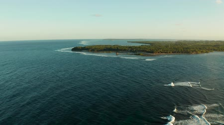 luna : Popular surf spot called cloud 9 on the island of Siargao and surfers on the waves at sunset, top view.