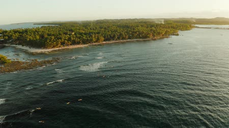 siargao island : Surf spot with surfers on the waves at sunset on the island of Siargao, cloud 9, Philippines. Aerial view.