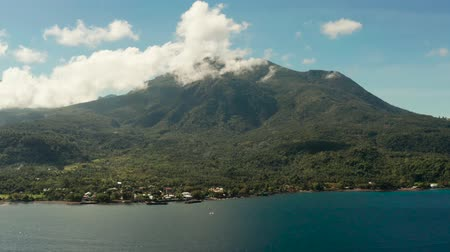 mindanao : Sea and Mountains covered rainforest, trees and blue sky with clouds, aerial view. Camiguin, Philippines. Mountain landscape on tropical island with mountain peaks covered with forest. Slopes of mountains with evergreen vegetation.