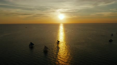 boracay : Sunset over the sea surface with sailing boats from above Boracay, Philippines. Reflected sun on a water surface. Sunset over ocean. Seascape, Summer and travel vacation concept Stock Footage
