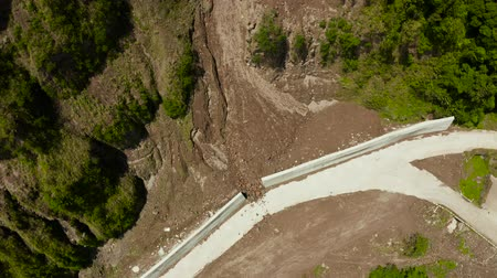 landslide : Protective concrete barrier to protect the mountain road from landslides and rock falls. Landslides and rockfalls on the road in the mountains. Stock Footage