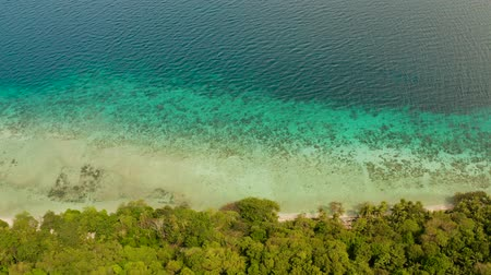 mořská voda : Seascape island coast with forest and palm trees, coral reef with turquoise water, aerial view. Sea water surface in lagoon and coral reef. Coastline of tropical island covered green forest near at sea Camiguin, Philippines