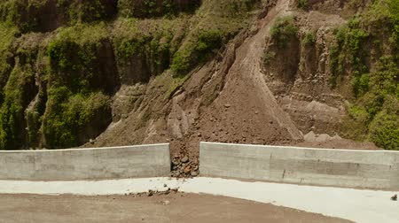 landslide : Mountain landslide and rock falls in an environmentally hazardous area. Large cracks in earth, Descent of large layers of earth blocking road. Soil under condition of the erosion as the cliff by human Stock Footage