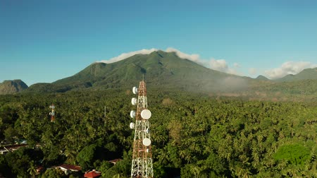 alıcı : Antennas and microwaves link dishes of mobile phone network and TV transmitter on telecommunication towers with mountains and rainforest. Camiguin, Philippines
