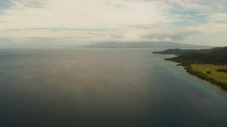 mindanao : Coastline of tropical island covered with green forest against the blue sky with clouds and blue sea, aerial view. Seascape: Ocean and sky.Philippines, Camiguin. Stock Footage