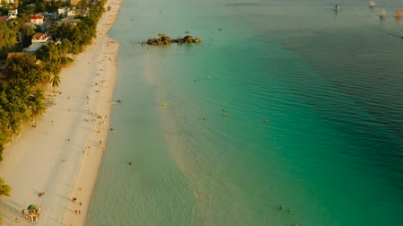 boracay : Topical white beach from above at sunset with tourists and sailing yachts on Boracay Island. Tropical white beach with sailing boat. Summer and travel vacation concept. Stock Footage