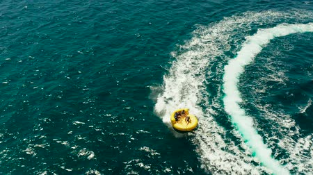 gonflable : Happy people ride the inflatable watercraft raft. Sea attraction, top view. Summer and travel vacation concept. Water sports and recreation on a tropical island.