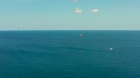 parachuting : People flying on a colorful parachute towed by a motor boat, aerial view. Parasailing in blue sky. Stock Footage