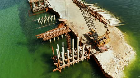 サスペンション : Pile driver hammer in action. Construction bridge over the sea bay on the tropical island of Siargao.