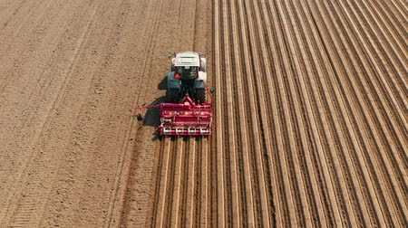 plowed land : aerial view tractor cuts furrows in farm field for sowing farm tractor with rotary harrow plow preparing land for sowing. Tractor with harrows prepares the agricultural land for planting crop. Cultivation of farmland by disc harrows.