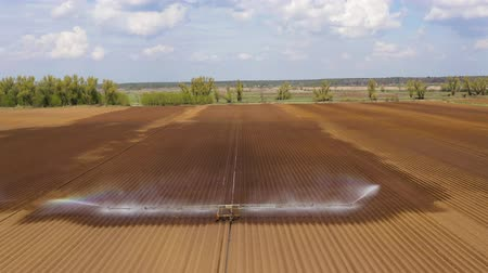 spil : aerial view crop irrigation machine using center pivot sprinkler system. An irrigation pivot watering agricultural land. Irrigation system watering farm land.