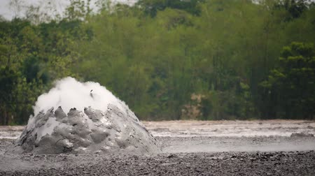 gejzír : mud volcano with bursting bubble bledug kuwu. volcanic plateau with geothermal activity and geysers, slow motion Indonesia java. volcanic landscape
