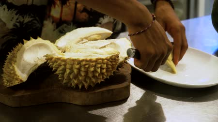 mal cheiroso : hand peeling and cuts durian fruit. caucasian man peeling durian in kitchen room