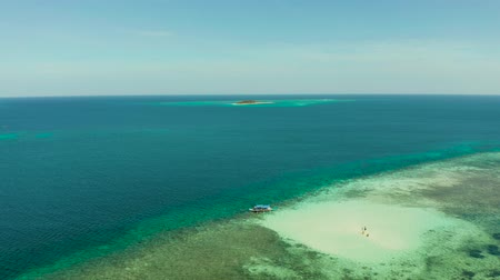 island hopping : Small sandy beach on a coral atoll in turquoise water, aerial view. Summer and travel vacation concept. Balabac, Palawan, Philippines.