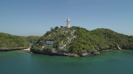 pellegrinaggio : Statue of Jesus Christ on Pilgrimage island in Hundred Islands National Park, Pangasinan, Philippines. Aerial view of group of small islands with beaches and lagoons, famous tourist attraction, Alaminos.