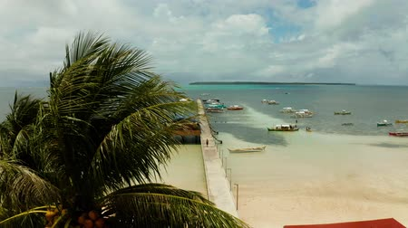 siargao island : Long pier with moored boats on the beach, aerial view. General Luna, Siargao island.