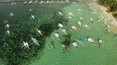 travel theme : Boats waiting for tourists on a tropical beach in blue water, aerial view. Summer and travel vacation concept.